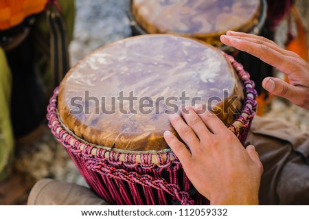 Man playing the djembe (african drum) outdoors - stock photo