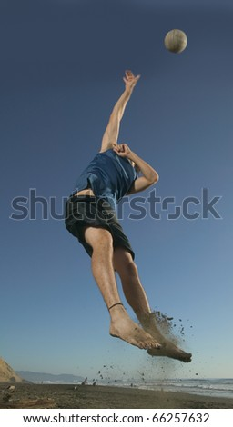Man playing volleyball on beach - stock photo