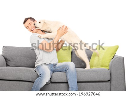 Man playing with a puppy seated on sofa isolated on white background - stock photo