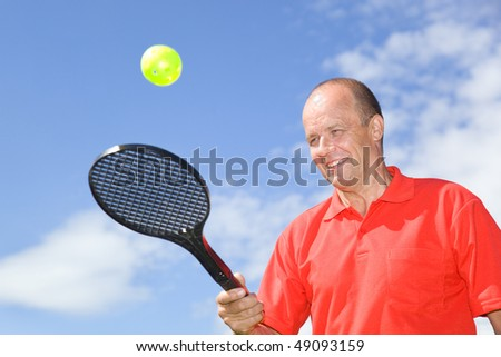 Man playing with a racket and a ball - stock photo
