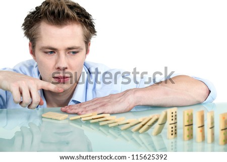 Man playing with dominoes - stock photo