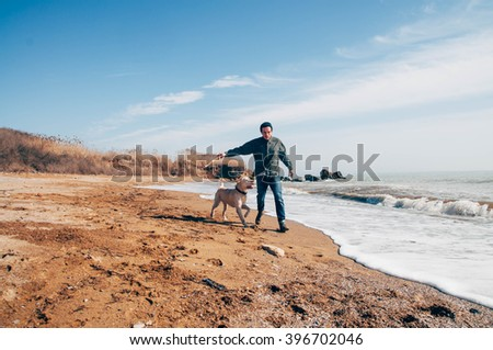 man playing with labrador dog on beach - stock photo