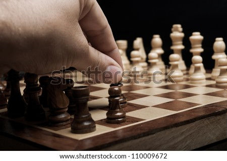 man plays chess and makes the first move a pawn - stock photo
