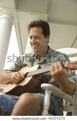 Man plays guitar while sitting in a rocking chair on a porch. Vertical shot. - stock photo
