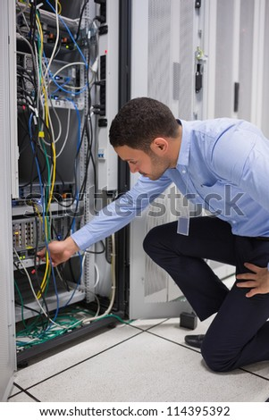 Man plugging a cable into server in data center - stock photo