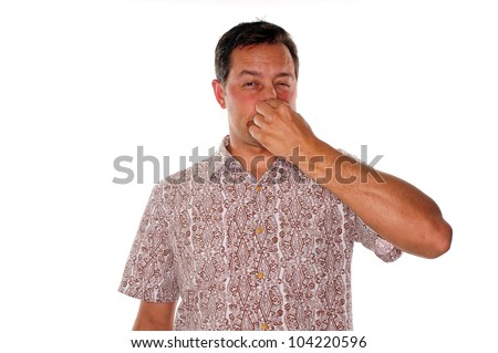 Man plugging nose after smelling a very bad stench - stock photo