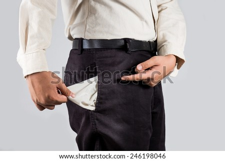 Man pointing at his empty pocket - stock photo
