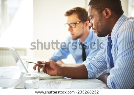 Man pointing at laptop for his colleague - stock photo