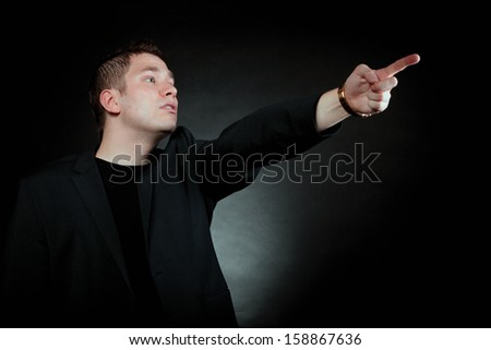 man pointing at something interesting showing your product black background