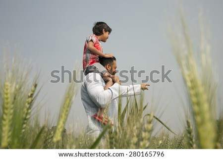 Man pointing at something while carrying little boy on shoulders - stock photo