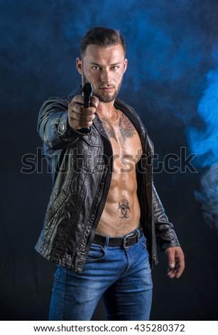 Man pointing gun to camera, wearing jacket on naked torso - stock photo