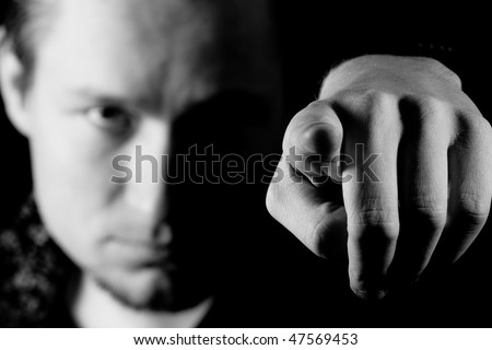 Man pointing his finger at you isolated on black - stock photo