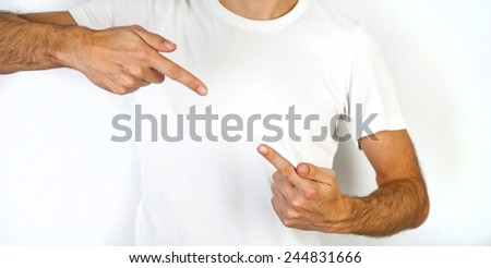 Man pointing inwards with the index finger of both hands from the top and bottom diagonal corner towards blank copyspace in between on his chest in a plain white t-shirt - stock photo