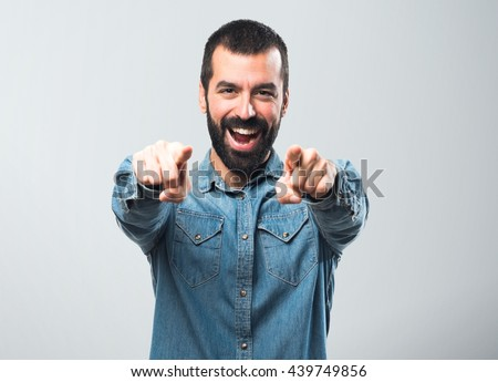 Man pointing to the front over grey background - stock photo