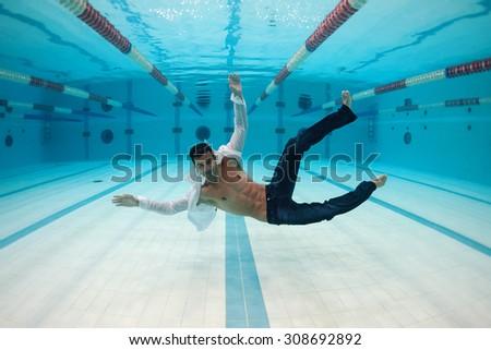 Man portrait wearing white shirt inside swimming pool. Underwater image. - stock photo