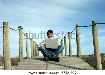 man portrait with computer on a beach landscape
