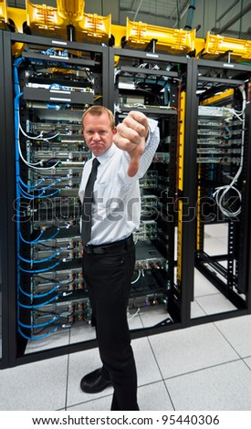 Man posing a thumbs-down in front of data center server racks. - stock photo