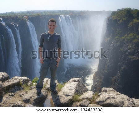 Man posing against Victoria Falls in Zimbabwe, Africa - stock photo