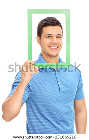 Man posing behind a green picture frame isolated on white background - stock photo