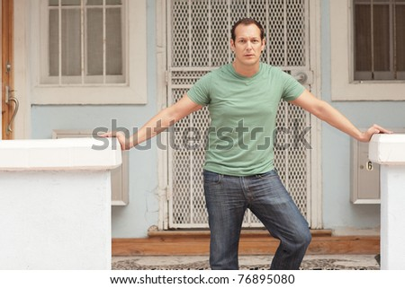 Man posing by a building - stock photo