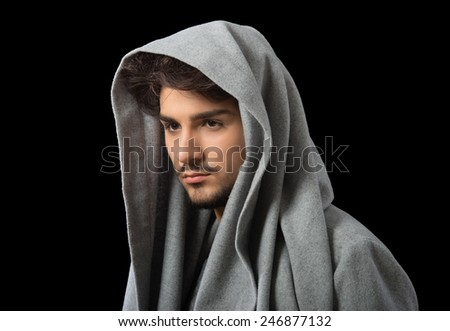 Man posing in gray cowl neck hoodie, studio portrait, dark background - stock photo
