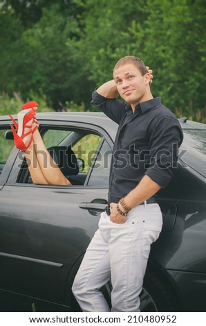 Man posing near the car with woman legs out the window. - stock photo