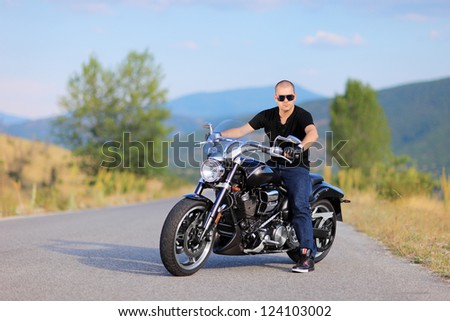 Man posing on a costume made motorcycle on the road - stock photo