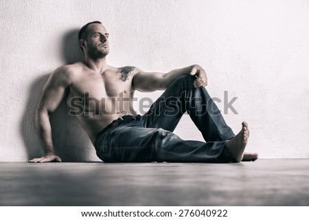 Man posing shirtless, leaning on white wall - stock photo
