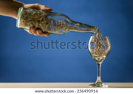 Man pouring a tangled mass of string from a transparent wine bottle into a wineglass in a conceptual image over blue with copyspace - stock photo