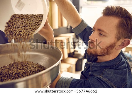 Man pouring coffee beans into a roasting machine - stock photo