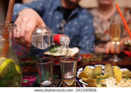 Man pouring vodka in the asian restaurant - stock photo