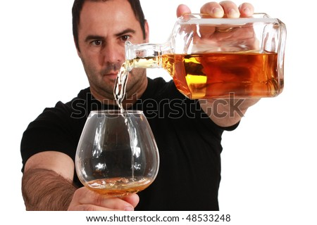 Man pouring whiskey into a glass, focus in the glass and bottle