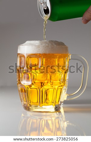 Man pours beer from can to a mug  - stock photo