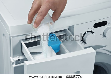 Man pours detergent into the washing machine - stock photo