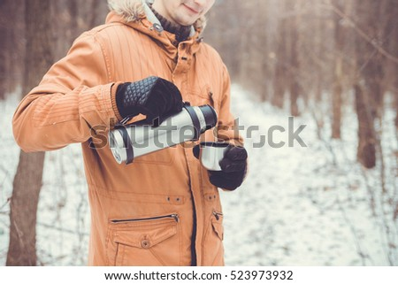 Man pours tea out of thermos. Winter forest. Close-up