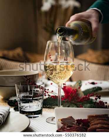 Man pours white wine into a glass