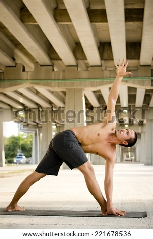 Man practicing advanced yoga in a urban background - stock photo