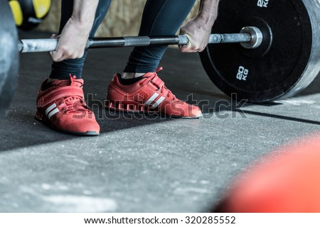 Man practicing weight lifting in the exercise room - stock photo