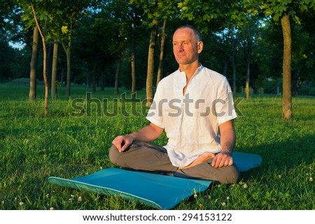 Man practicing yoga in the park at sunrise - stock photo