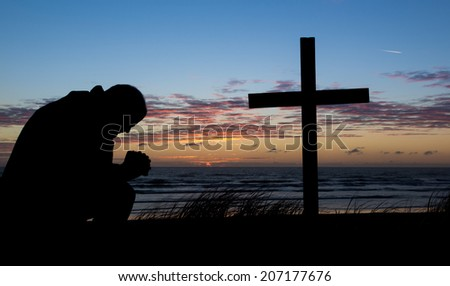 Man praying by a cross at the beach while the sunset for another day. - stock photo