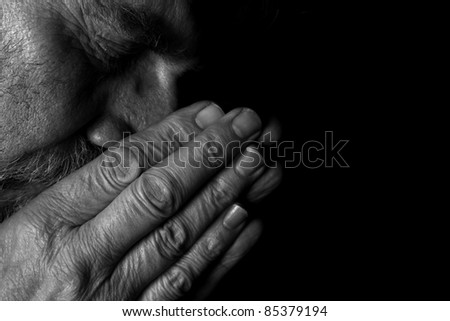 Man praying in darkness - stock photo