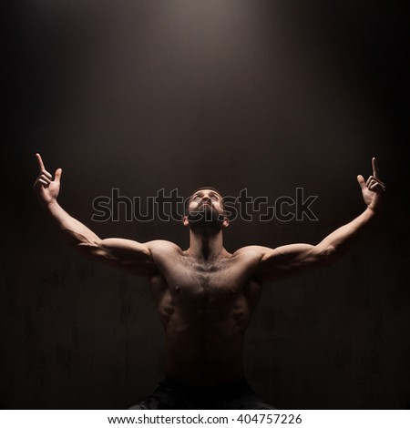 Man praying on dark studio background