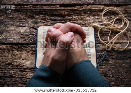 man praying on the Bible selective focus - stock photo