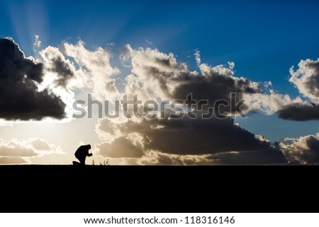 Man praying outlined against a beautiful sunset - stock photo