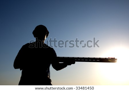 Man preparation for shooting with his gun silhouette - stock photo