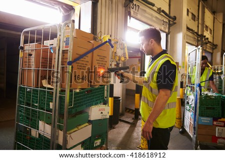 Man prepares and scans packages in a warehouse for delivery - stock photo