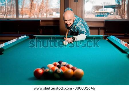 Man prepares to smash the pyramid of billiard balls on the table. American pool billiard. Pool billiard game. Billiard sport concept. - stock photo