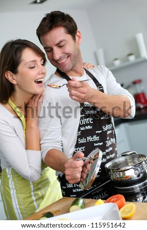 Man preparing dinner and making her wife taste the food - stock photo