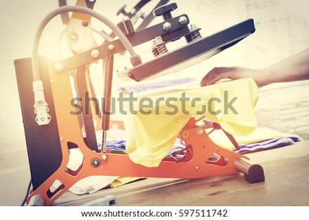 man preparing t shirt for printing in the silk screen printing machine - Pictures For Printing
