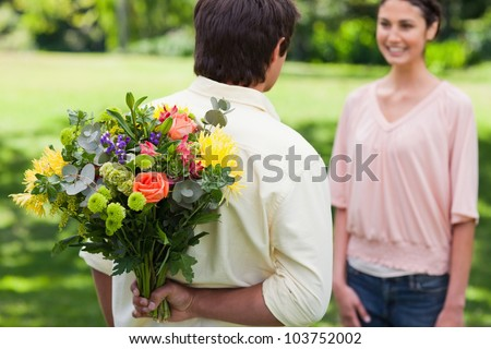 Man preparing to surprise his friend by giving her a bunch of flowers with focus on the man and the flowers - stock photo
